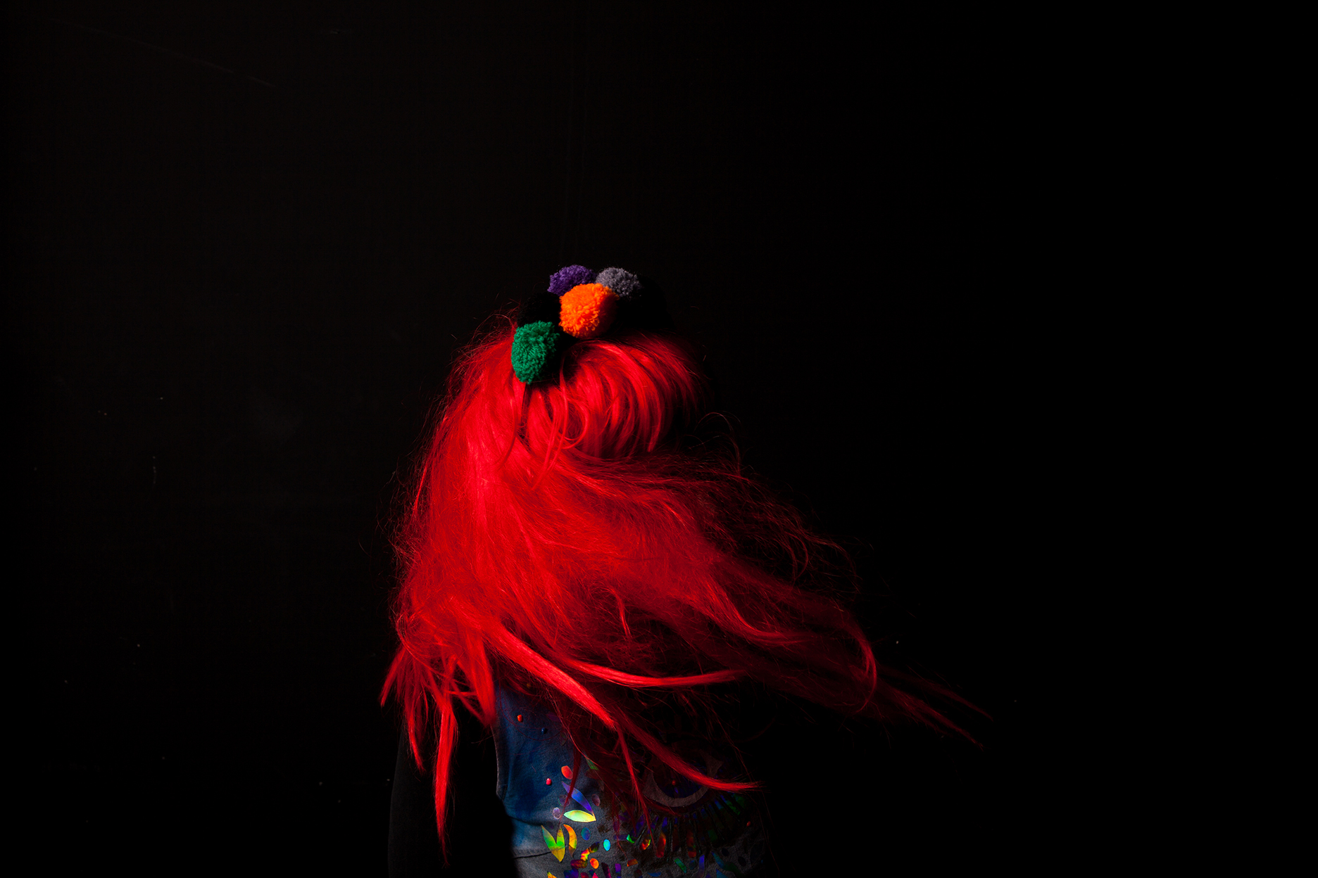 A black background, a body with bright red hair and a costume whirls